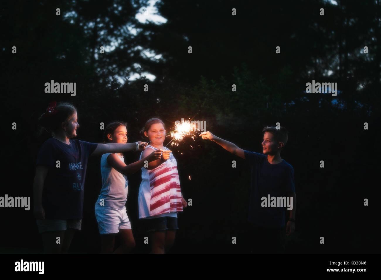 Garçon et trois filles d'allumer des cierges merveilleux ensemble de nuit le jour de l'indépendance, Photo Stock