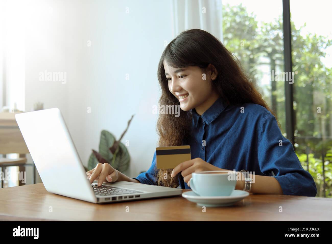Achats en ligne concept. jeune femme asiatique à l'aide d'ordinateur avec une carte de crédit pour les achats en Banque D'Images