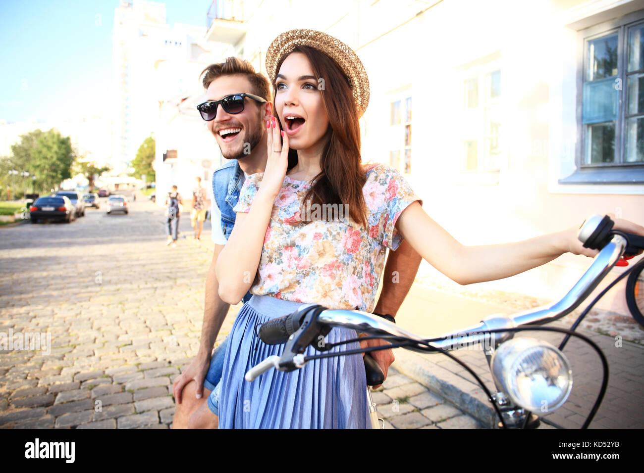 Happy young couple allant pour une promenade en vélo sur une journée d'été dans la ville.ils ont du plaisir ensemble. Banque D'Images