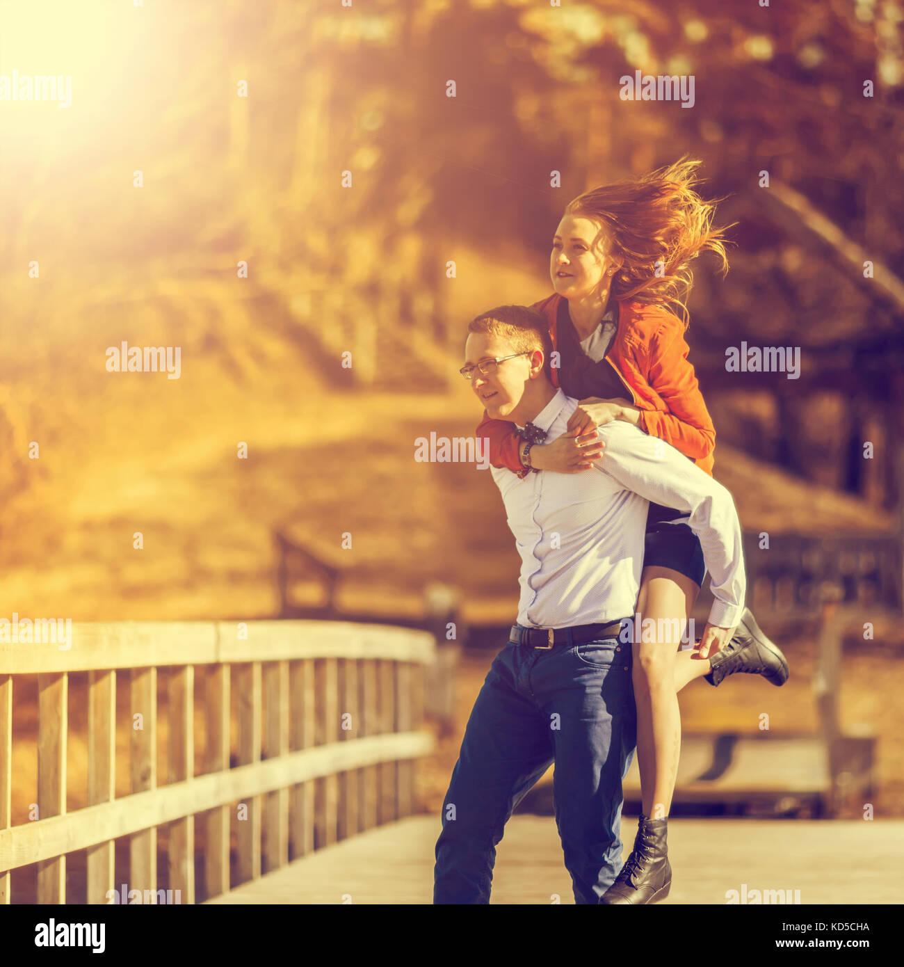 Heureux homme portant sa petite amie à l'arrière sur sur le pont sur la rivière. vintage tone Photo Stock