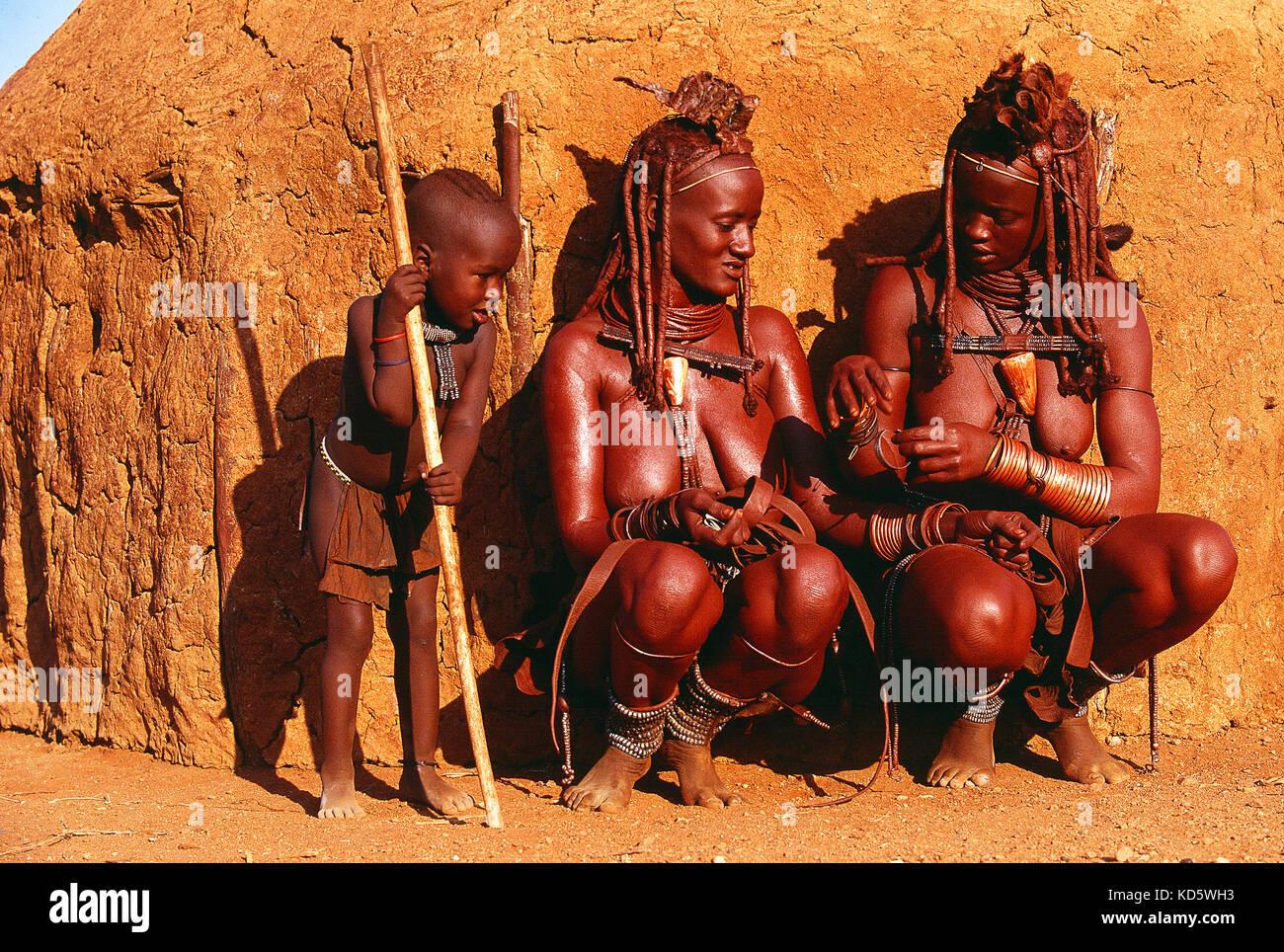 Namibie. Région de Kunene. Deux femmes Himba et un enfant près d'une hutte de boue. Banque D'Images