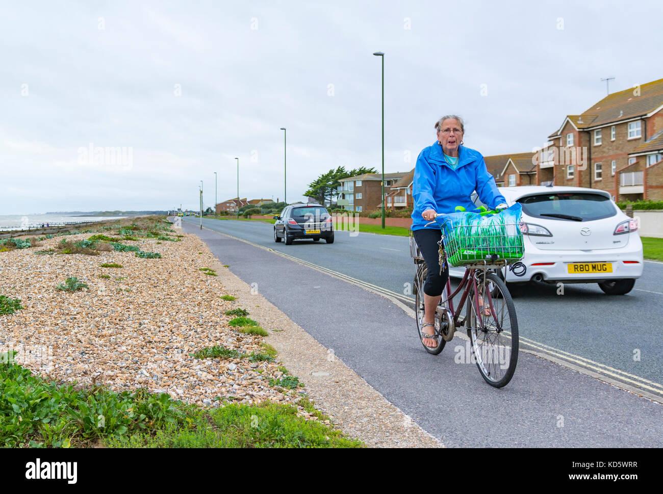 Femme âgée à vélo sur un trottoir au Royaume-Uni. Photo Stock