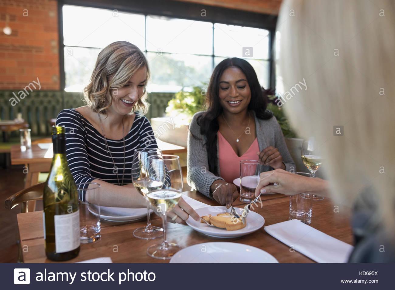Le partage d'amis femmes dessert et de boire du vin blanc, un repas à table de restaurant Photo Stock