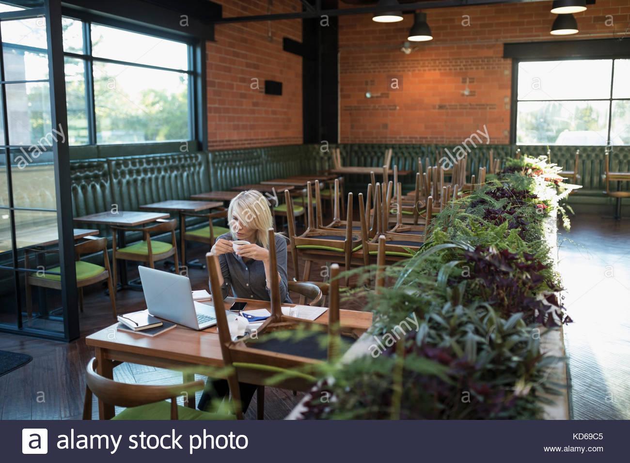 Propriétaire de l'entreprise cafe femme de boire du café et payer les factures, working at laptop Photo Stock