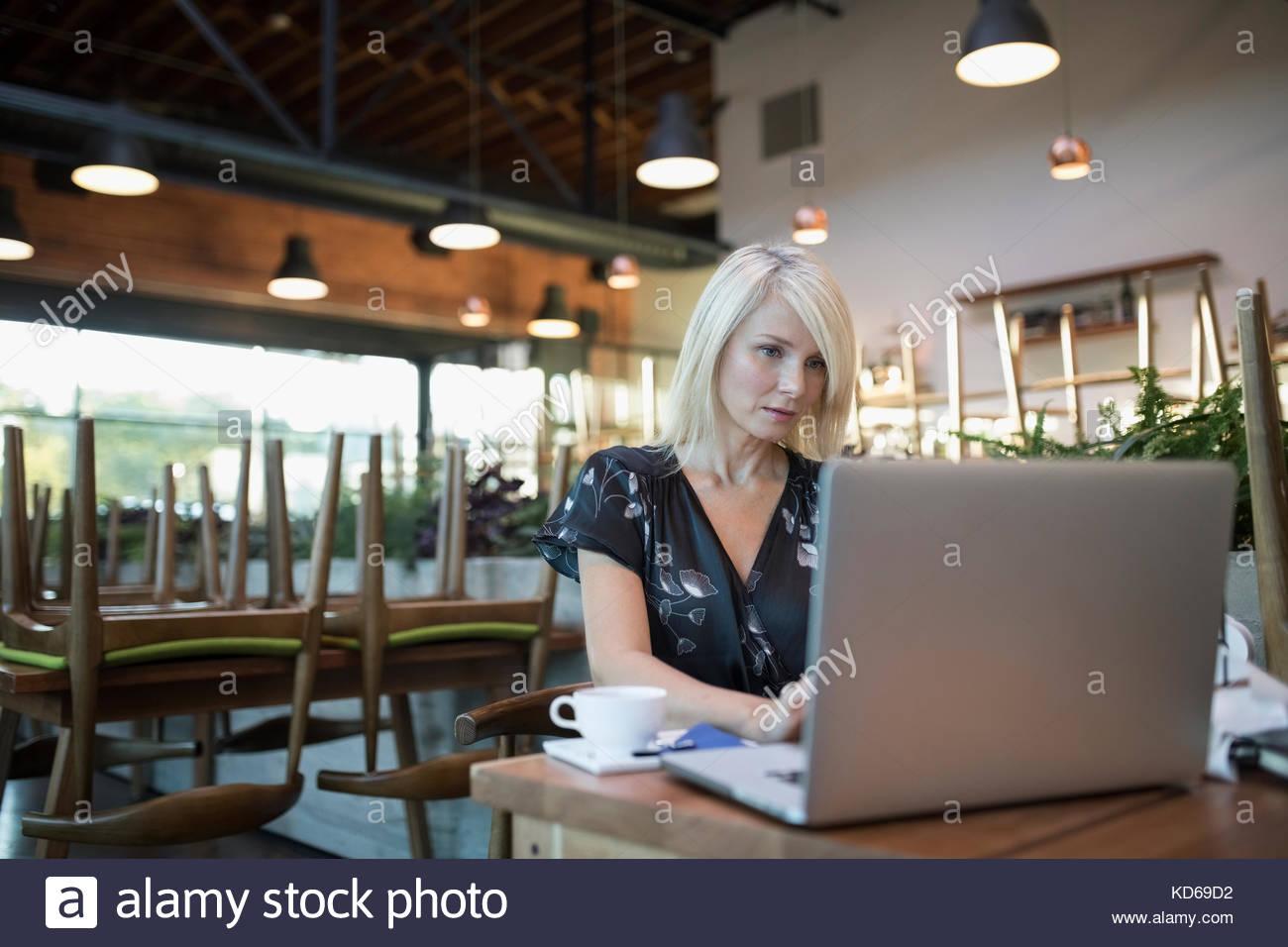 Café des femmes chef d'entreprise de payer des factures, working at laptop Photo Stock