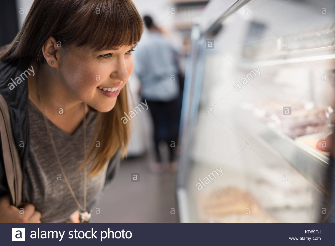 Smiling female customer browsing en cas d'affichage de la viande en boucherie Photo Stock