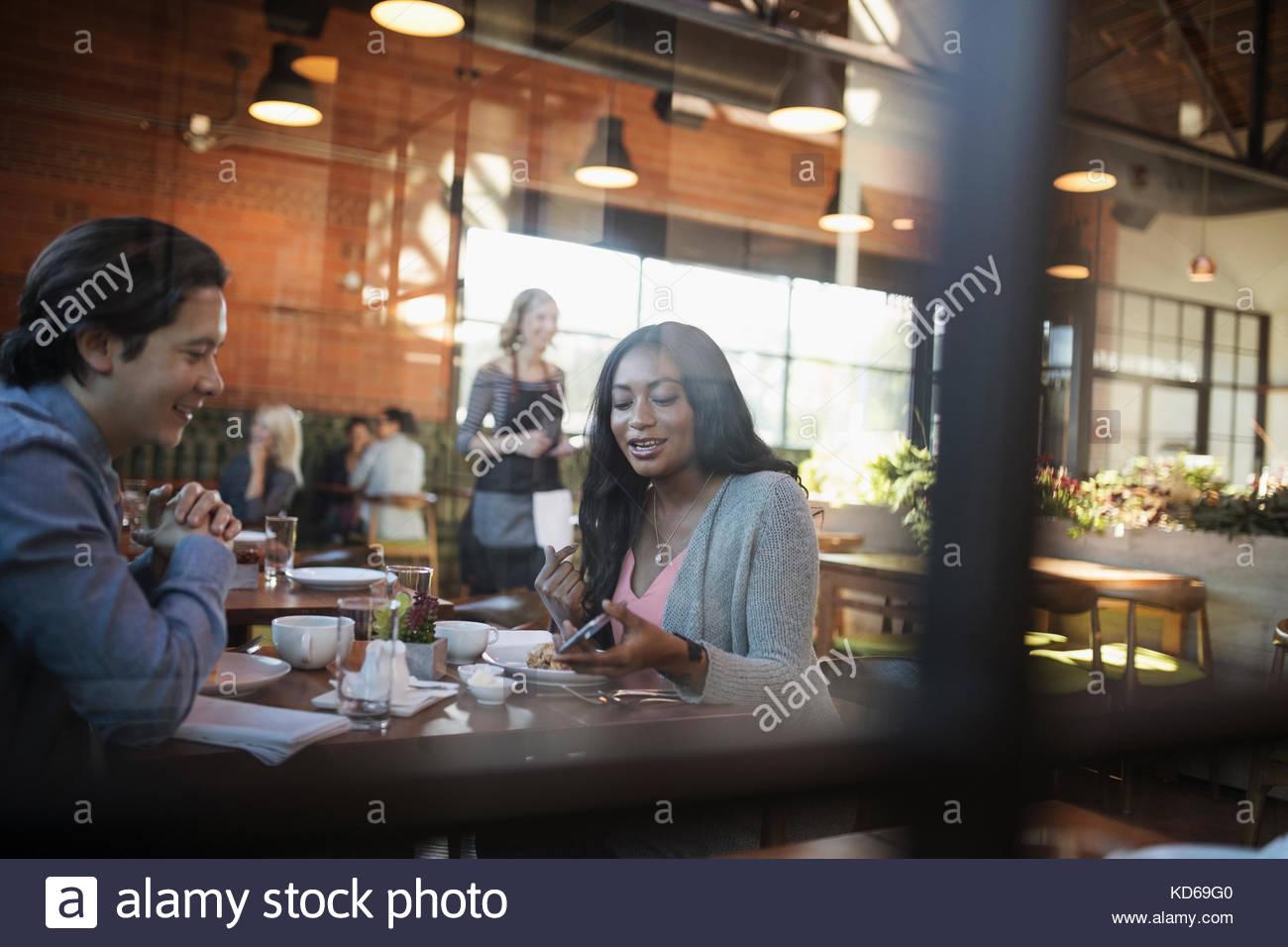 Couple using cell phone, dîner au restaurant table Banque D'Images