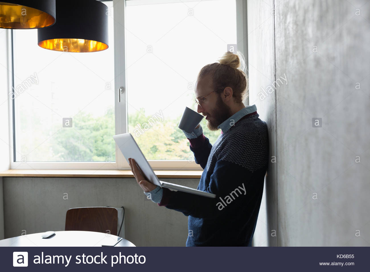 Businessman drinking coffee and using laptop in conference room Photo Stock