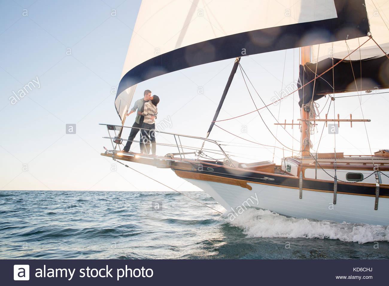 Affectionate couple kissing on voilier sur l'océan ensoleillé Photo Stock