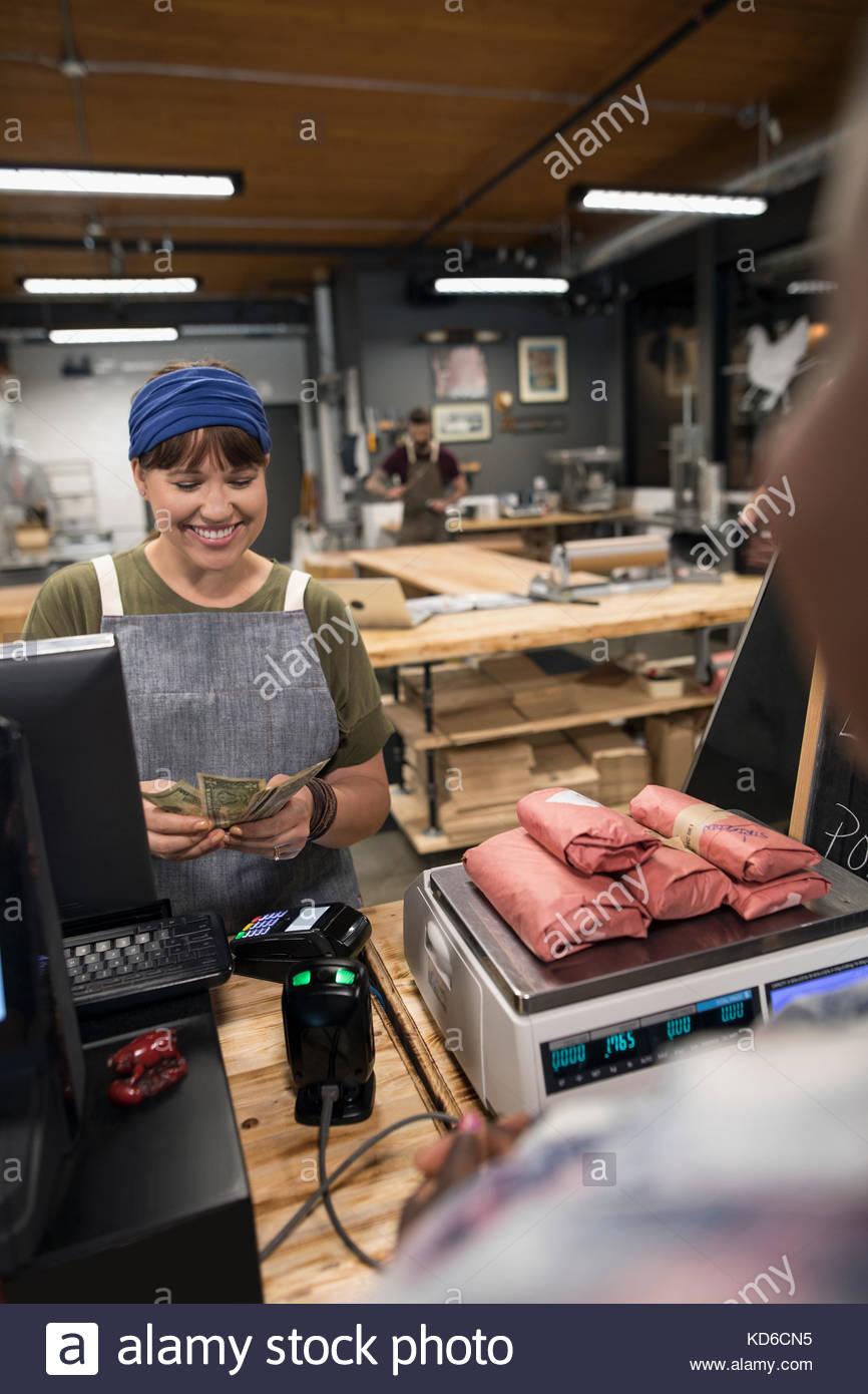 Femelles de boucherie compter les espèces de paiement du client dans butcher Photo Stock