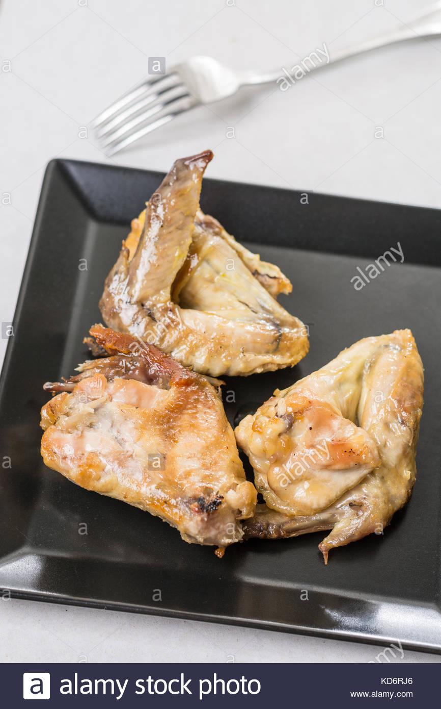 Closeup macro d'ailes de poulet frit servi sur la plaque carrée noire. Photo Stock