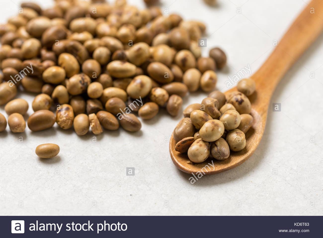 Tas de fèves de soja avec cuillère en bois sur la table en arrière-plan en marbre blanc. Photo Stock