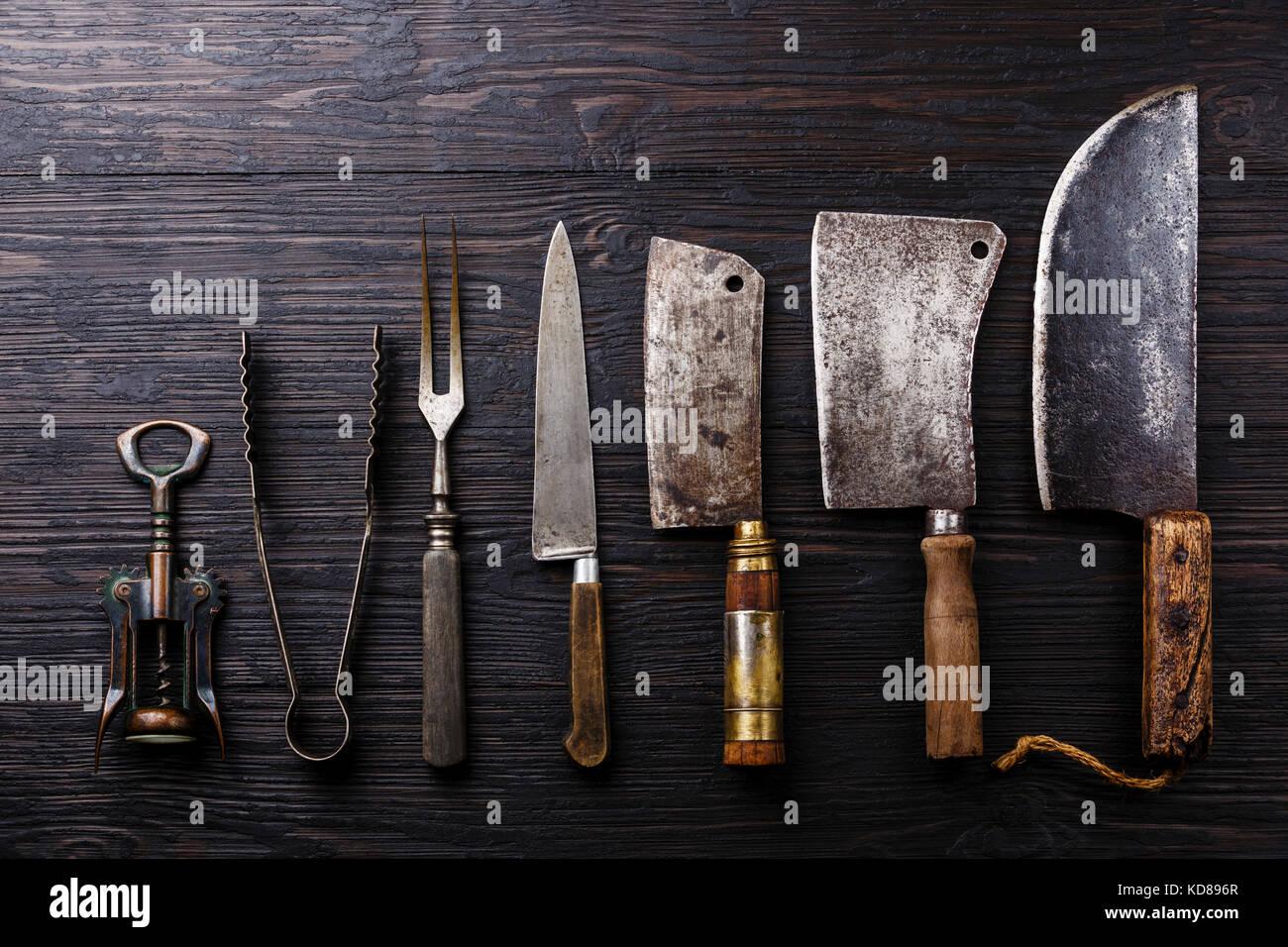 La viande de boucherie vintage gaillet, tire-bouchon et tongs sur fond de bois brûlé foncé Photo Stock