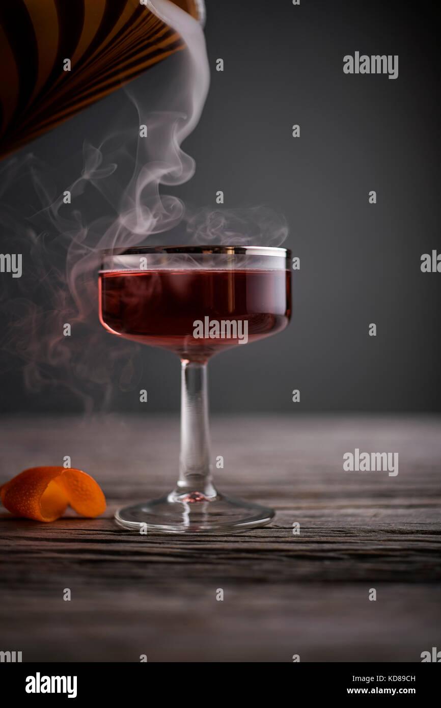 Cocktail rouge vintage en verre coupé avec la fumée qui en sur une surface en bois gris, rustique. Photo Stock