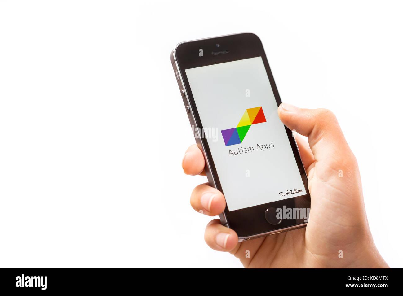 Un garçon à l'aide de l'app sur l'autisme un téléphone mobile Photo Stock