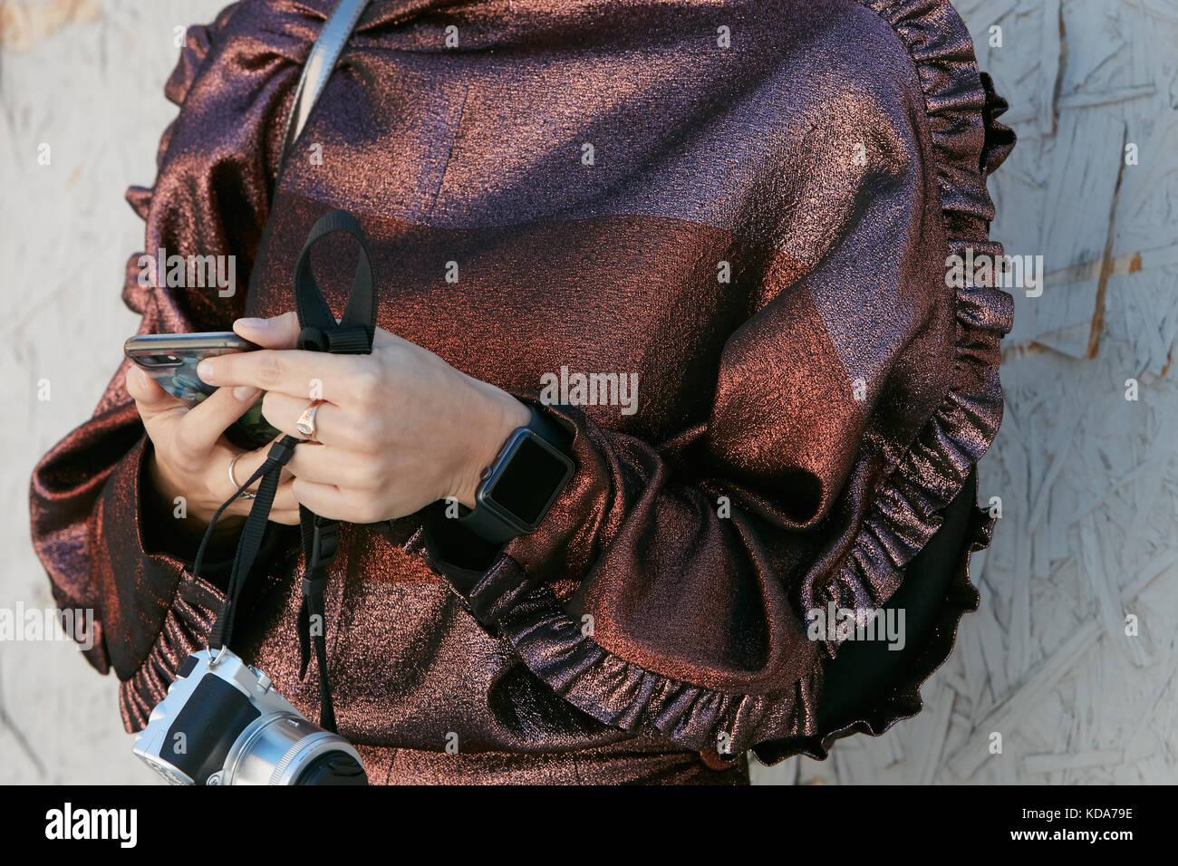Milan - 20 septembre: femme avec robe métallique bronze, montres et appareils apple looking at smartphone Photo Stock