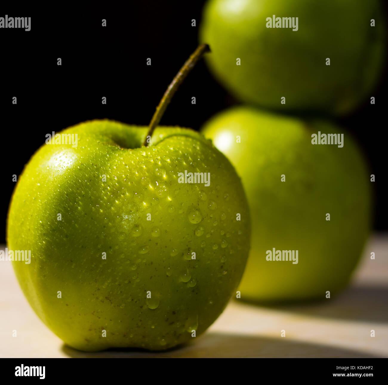 3 pomme verte, point sur le premier plan, arrière-plan foncé Photo Stock