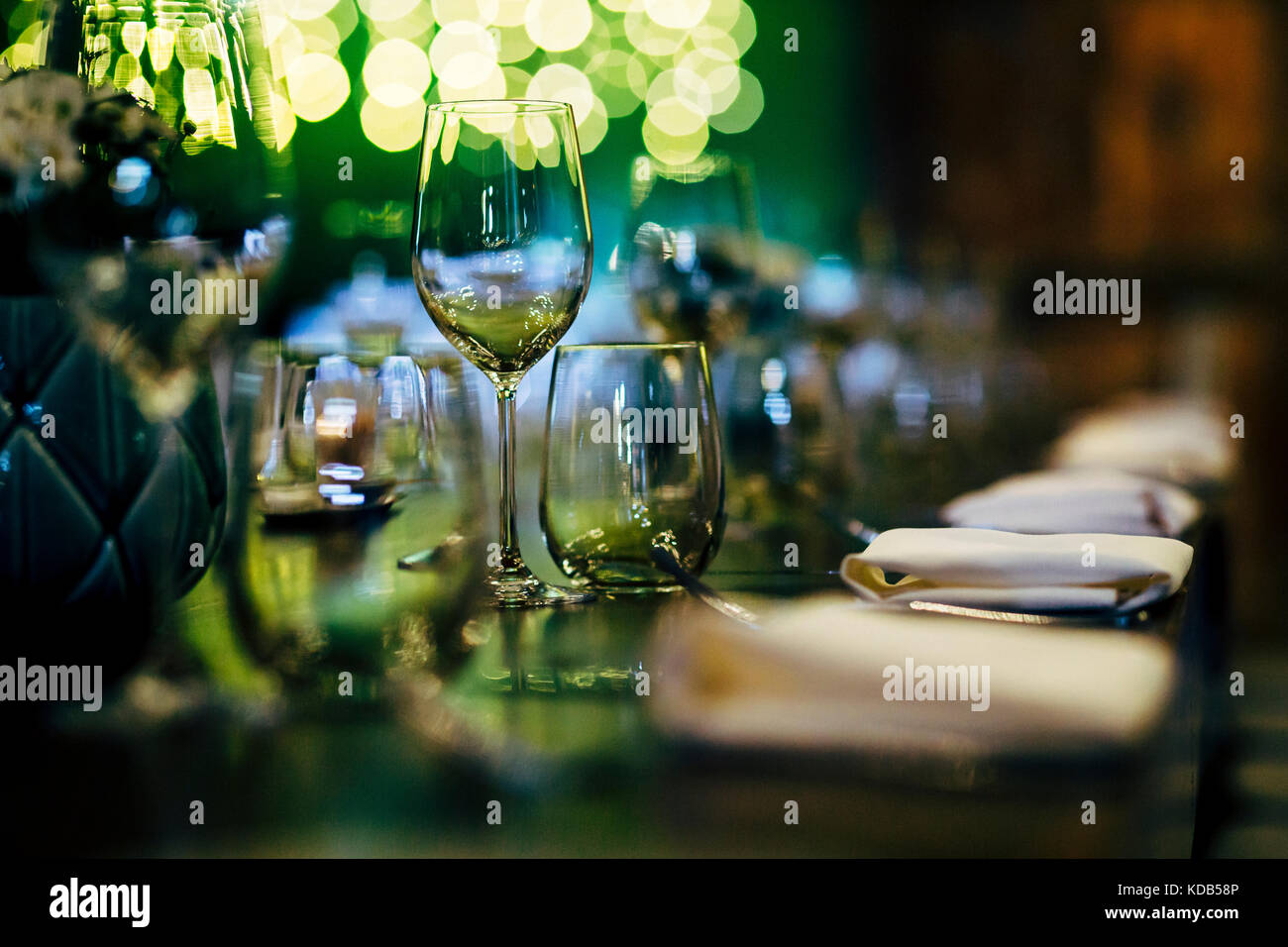 Les paramètres de table de luxe pour des repas avec et verrerie, belle arrière-plan flou. préparation Photo Stock