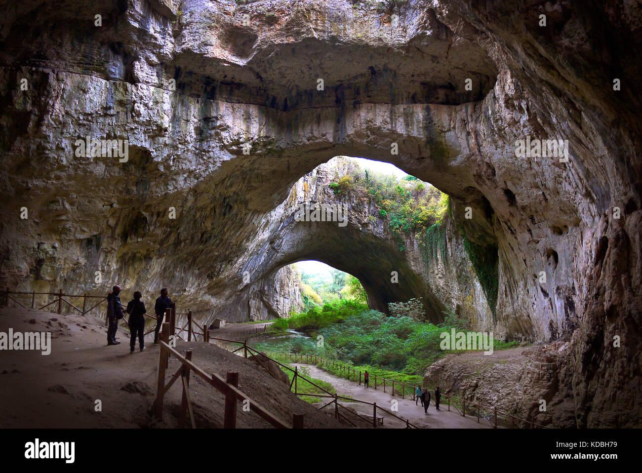 Visiteurs éclipsées par la taille de la grotte devetashka en Bulgarie. Photo Stock
