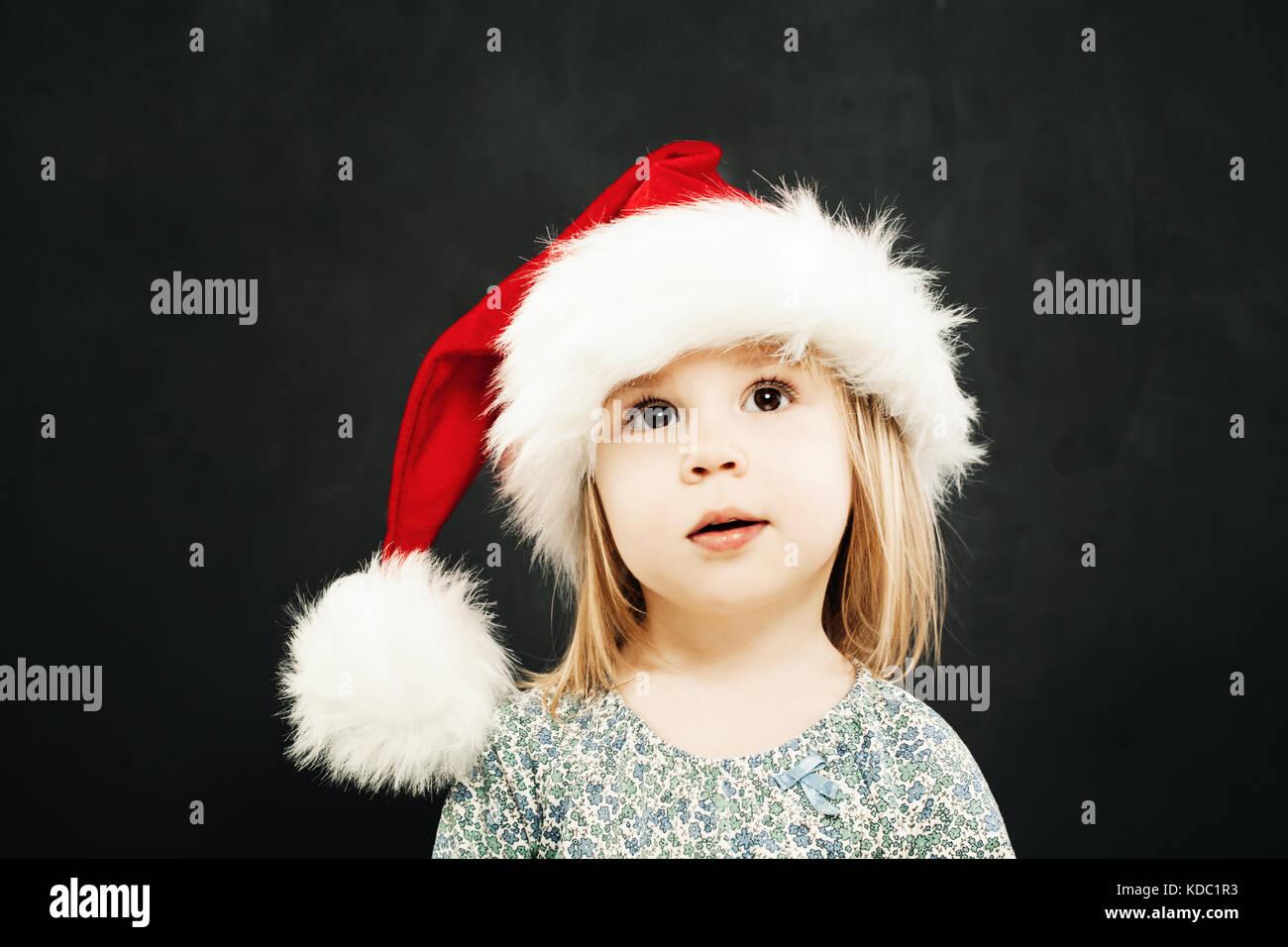 Noël des enfants girl in santa hat rêver sur fond noir Banque D'Images