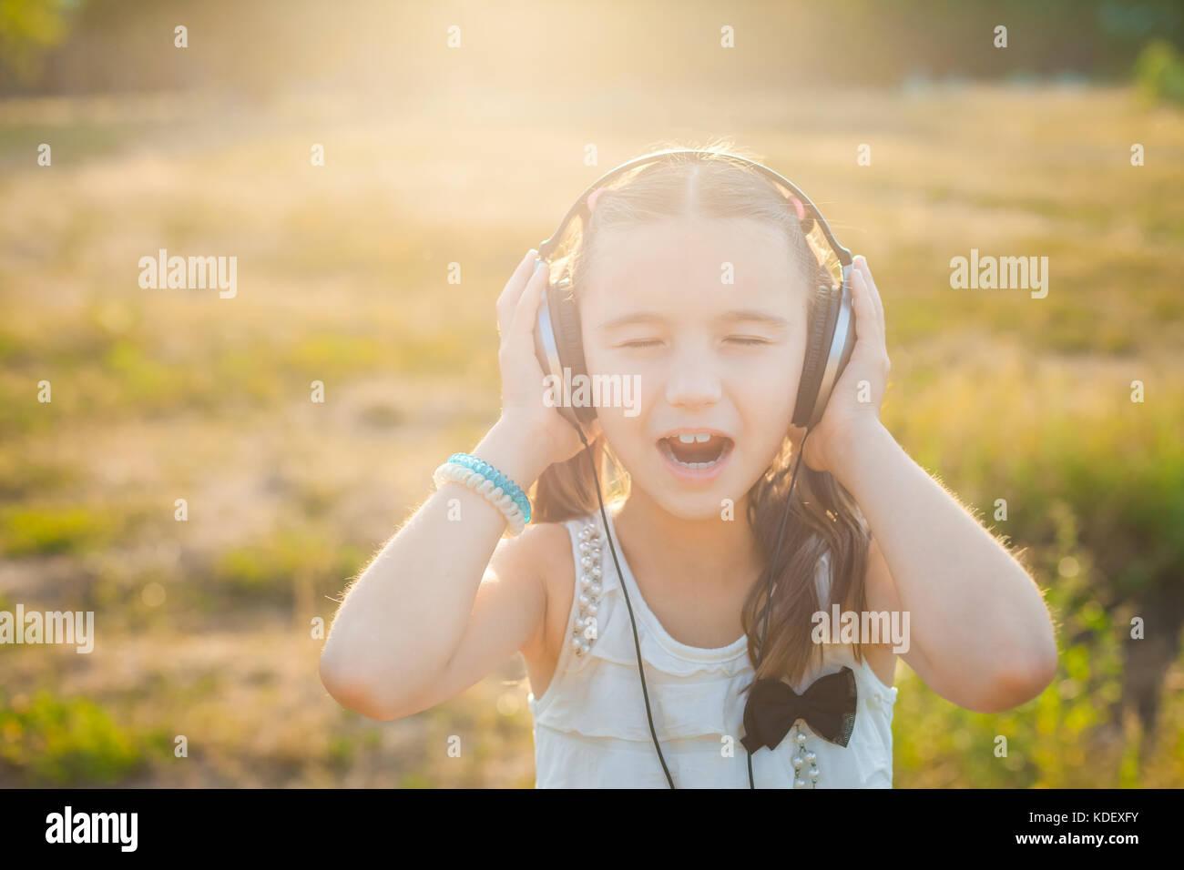 Petite fille à l'écoute de la musique avec des écouteurs Photo Stock