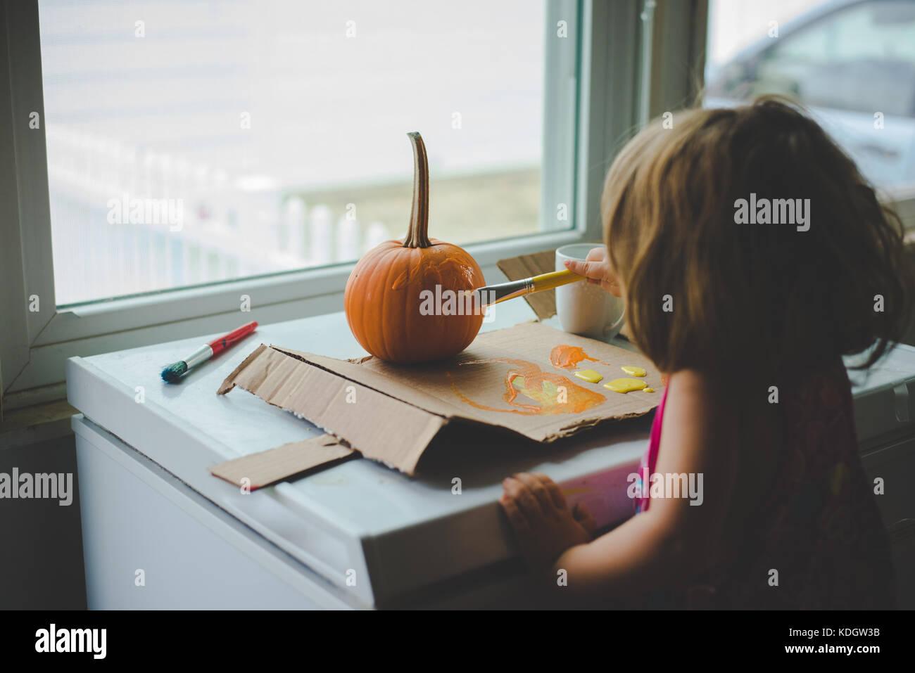 Une petite fille au cours d'activités d'automne citrouilles peintures. Banque D'Images