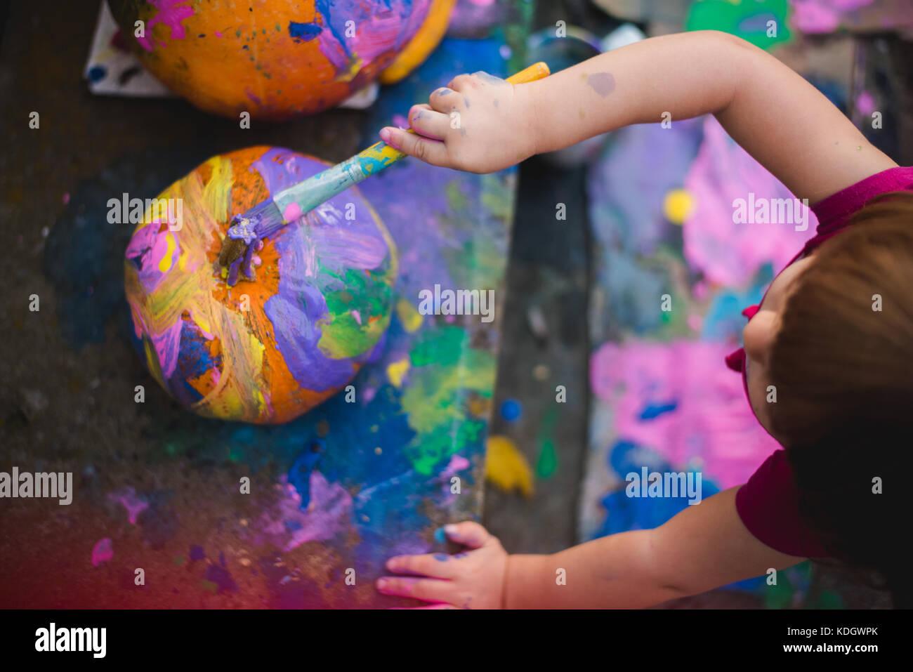 Une petite fille au cours d'activités d'automne citrouilles peintures. Photo Stock