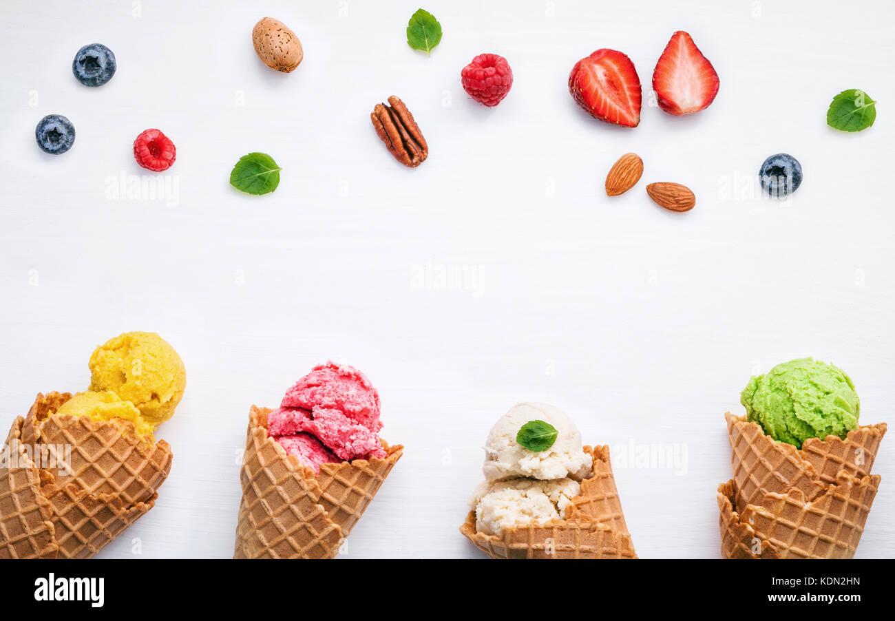 La crème glacée coloré avec les cônes et divers fruits bleuets Fraises Framboises ,,et feuilles Photo Stock