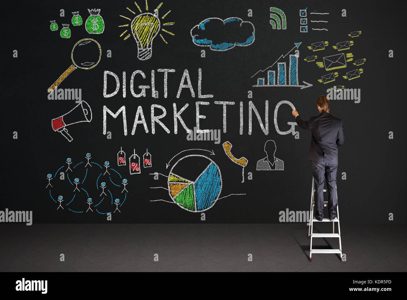 Vue arrière du businessman standing on staircase dessin digital marketing concept sur tableau noir Banque D'Images