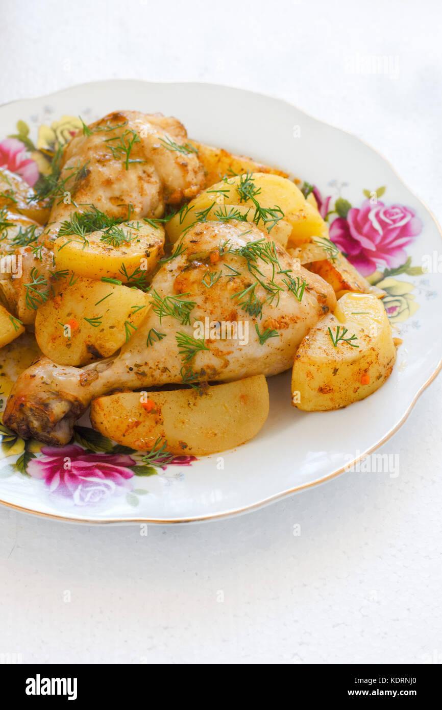 Cuisse de poulet rôti avec des pommes de terre on white plate Banque D'Images