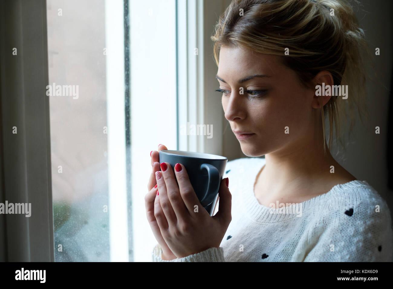 Sentiment de fille de mauvaise humeur et de boire une boisson chaude Photo Stock