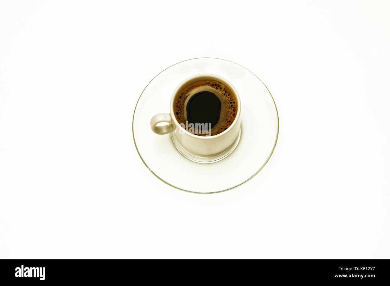 Une tasse de café sur une soucoupe en verre transparent sur fond blanc Photo Stock