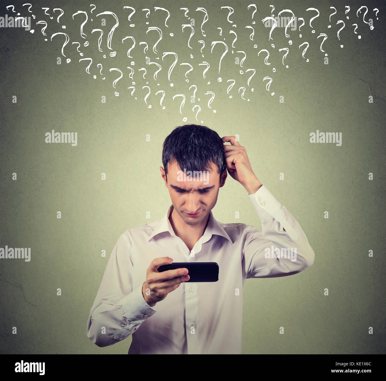 Portrait jeune homme confus en regardant son téléphone intelligent a de nombreuses questions isolé Photo Stock