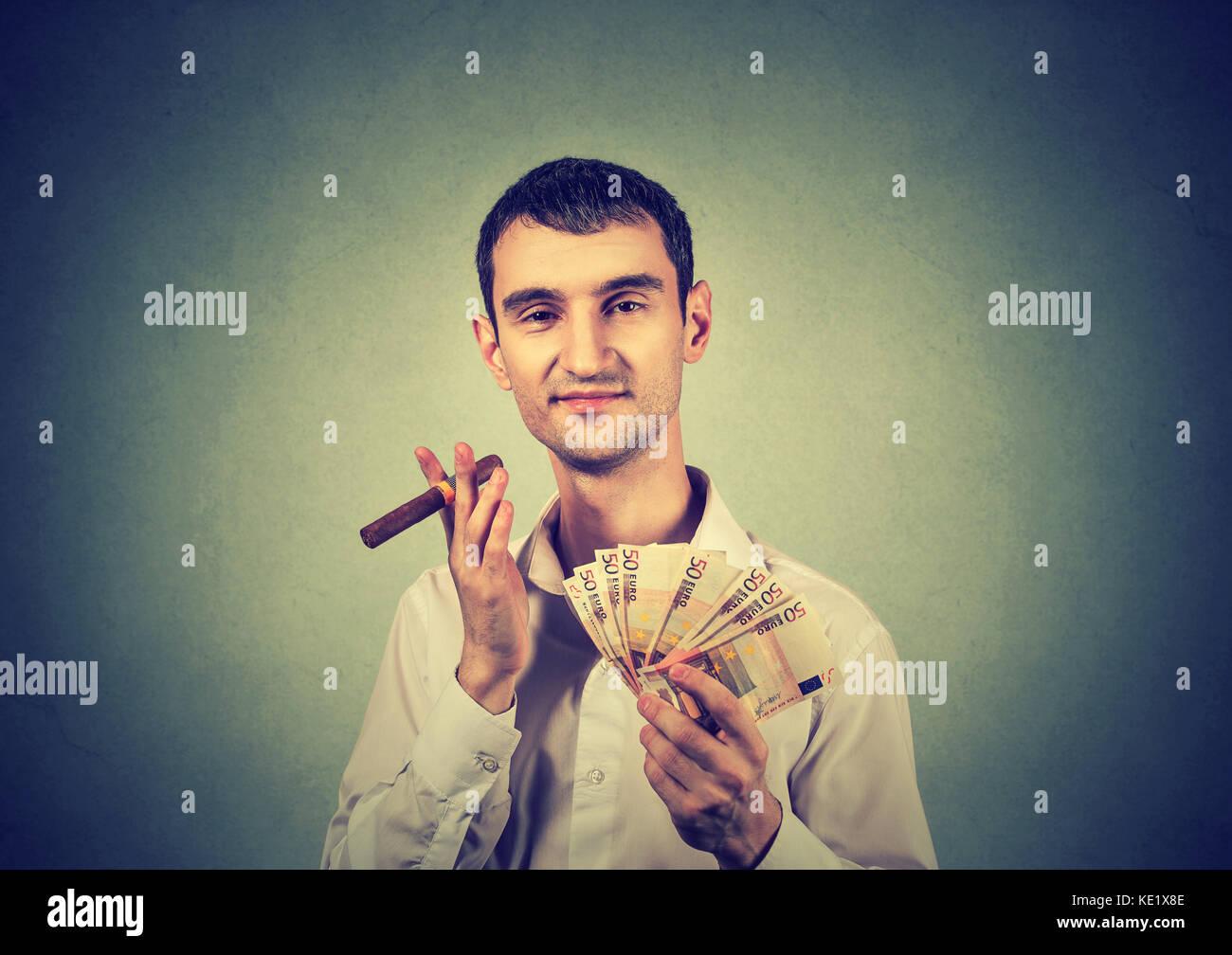Heureux jeune homme confiant avec l'argent des billets en euros et de cigare Photo Stock