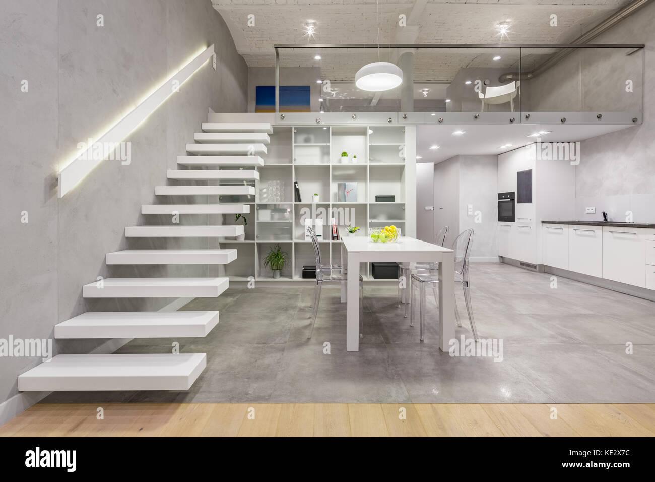 Loft avec mezzanine blanc escalier, table, chaises et cuisine ...