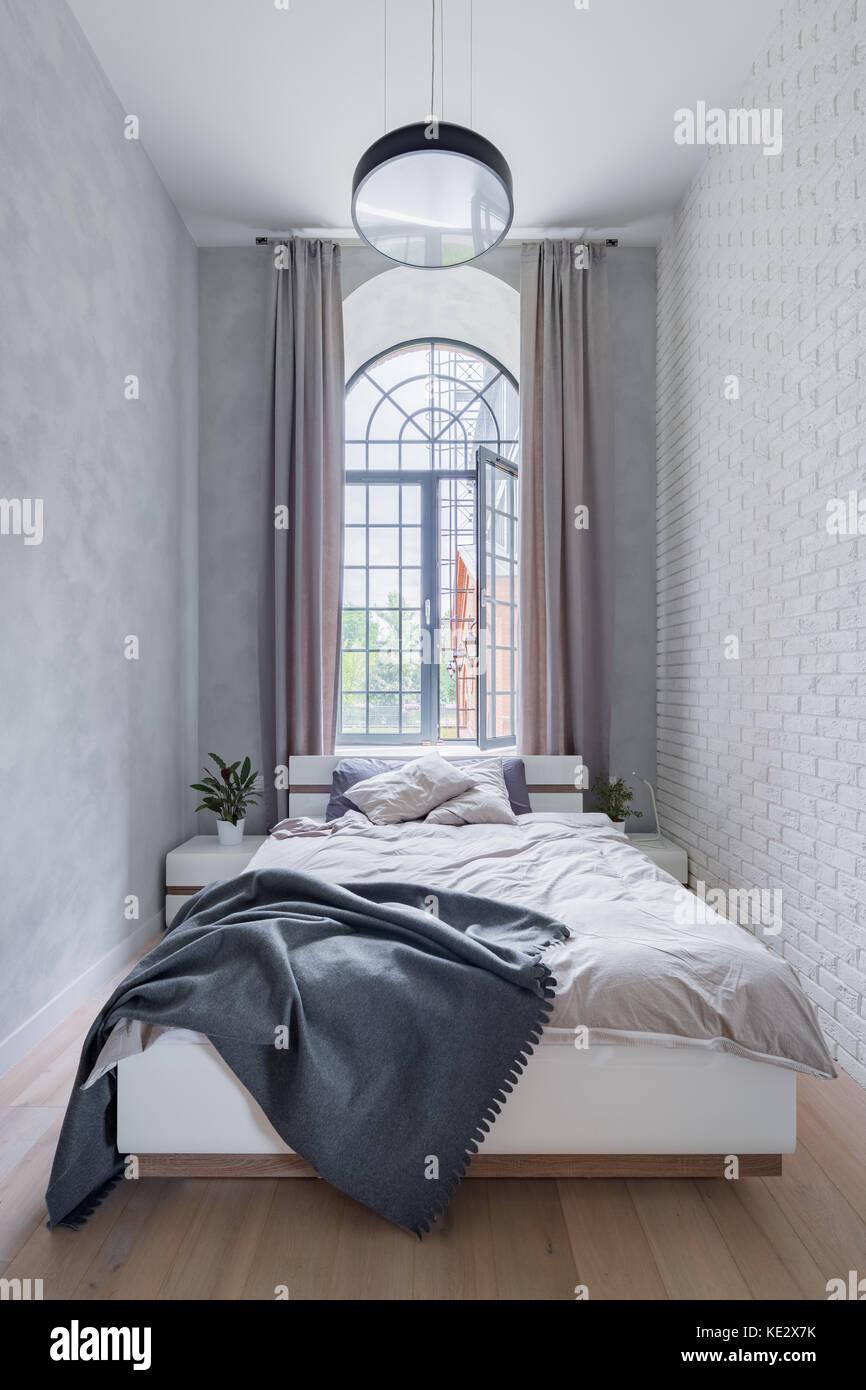Chambre en mezzanine avec lit double, grande fenêtre et mur en ...