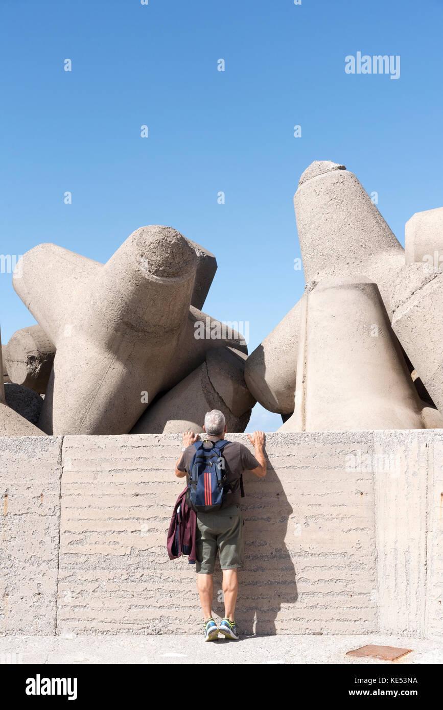 L'homme sur la pointe des pieds l'inspection de l'homme fait les blocs de béton, des tétrapodes, Photo Stock