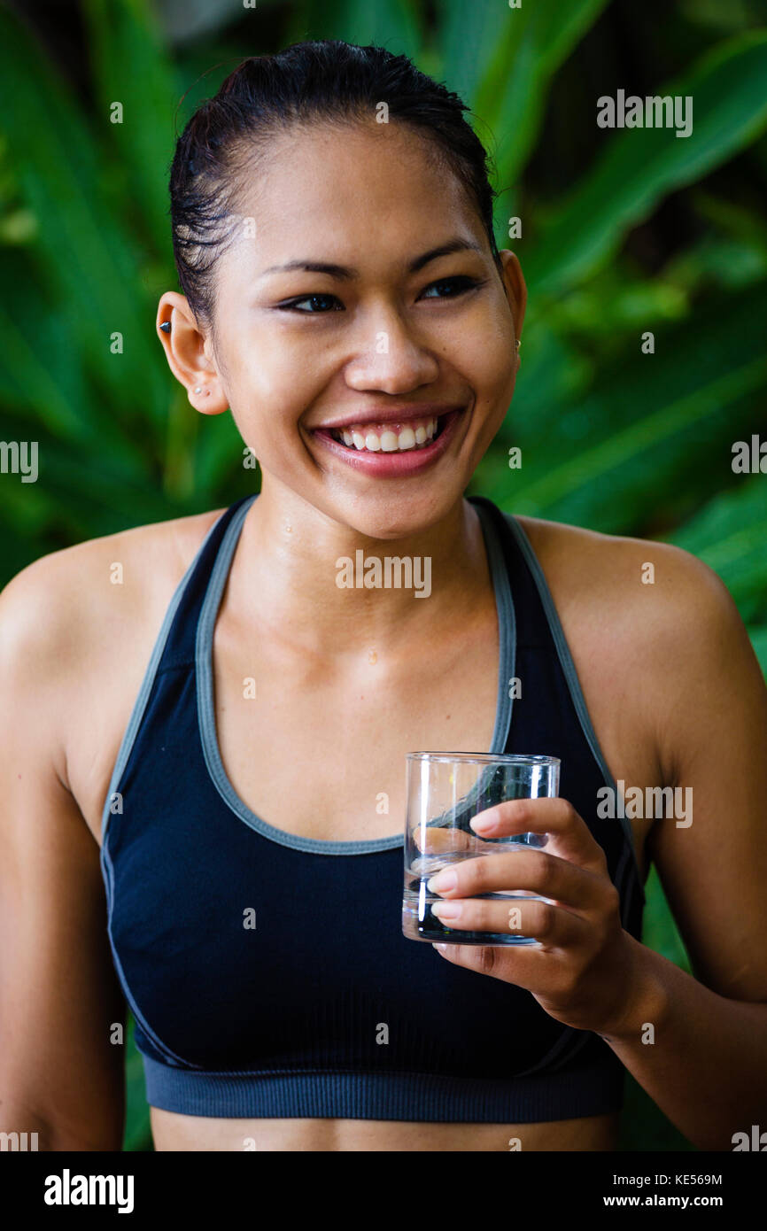 Asian Woman in fitness vêtements avec un verre d'eau, smiling Photo Stock