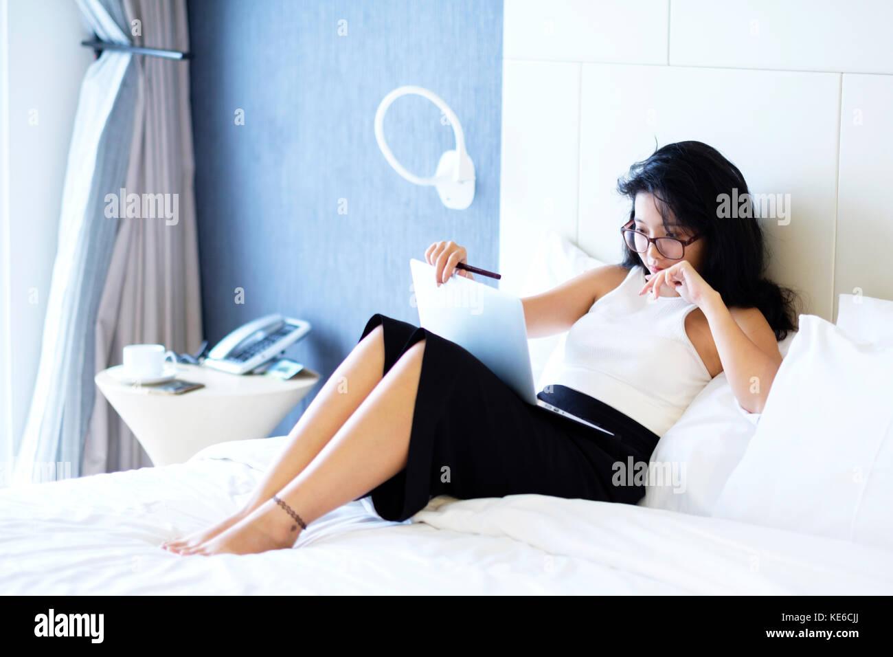 Young Asian business woman travaillant dans sa chambre d'hôtel Photo Stock
