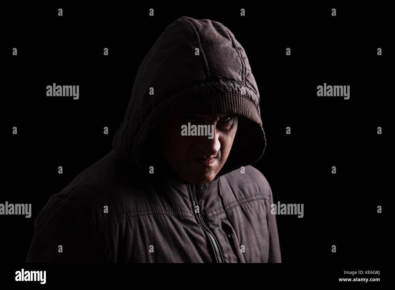 Avec l'homme et la colère refoulée instinct violents se cachant dans les ombres. debout dans l'obscurité Photo Stock