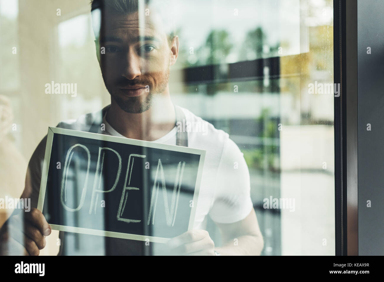 Waiter holding chalkboard with open word Photo Stock