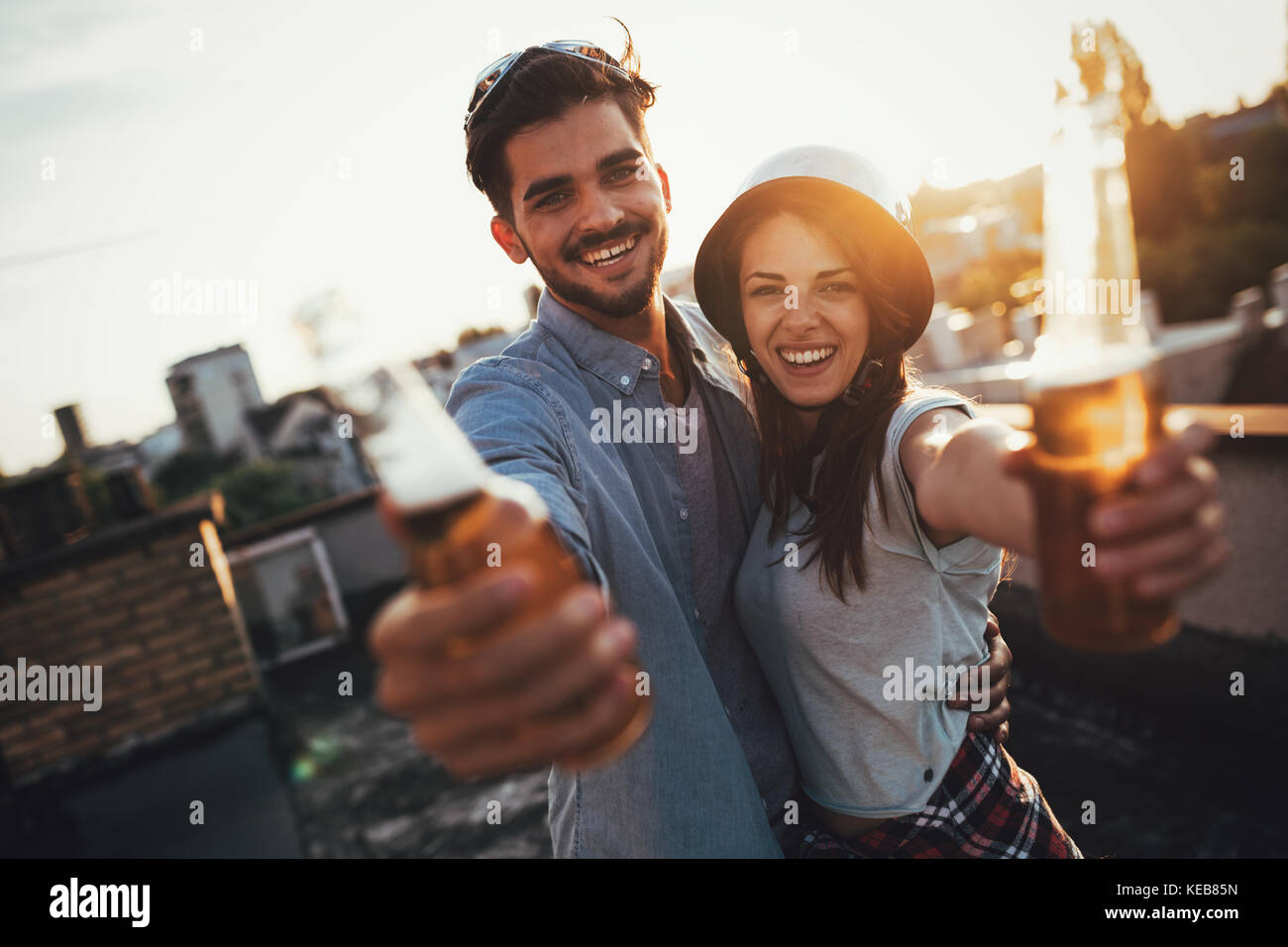 Young happy couple toasting with beer outdoors Photo Stock