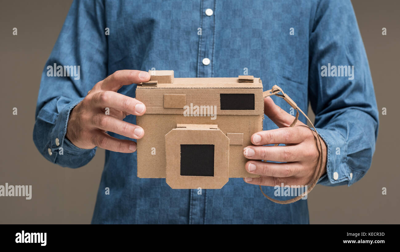 La tenue d'un photographe respectueux de la main de l'appareil photo en carton, de l'artisanat et la créativitéBanque D'Images