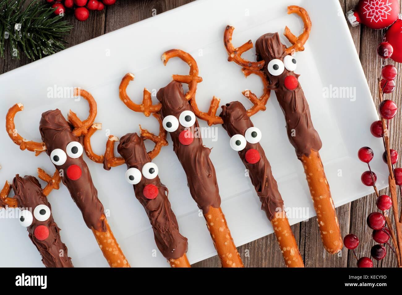 Le renne de noël mignon bretzel au chocolat, les tiges au-dessus sur une assiette de service blanc Banque D'Images