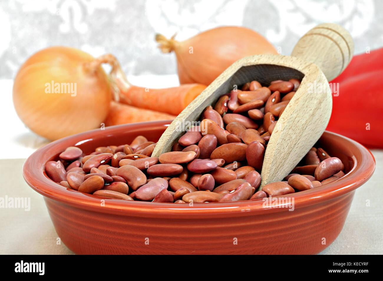 Les haricots crus avec une cuiller en bois dans un bol, selective focus macro avec copie espace. Photo Stock
