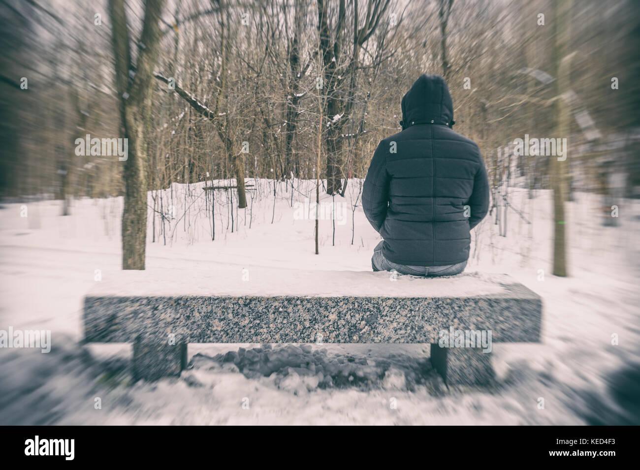 Homme assis sur un banc dans une forêt en hiver avec de la neige au sol Photo Stock