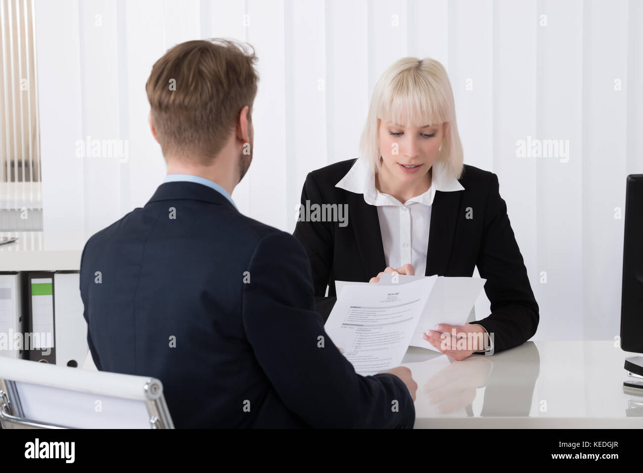 Young businesswoman discussing over reprendre avec candidat masculin in office Banque D'Images