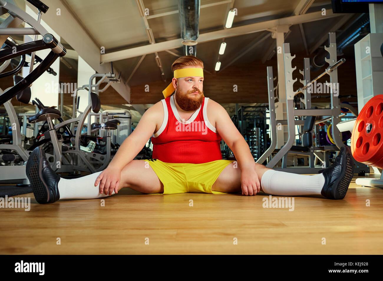 Drôle fat man fatigué assis sur le plancher dans la salle de sport Photo Stock