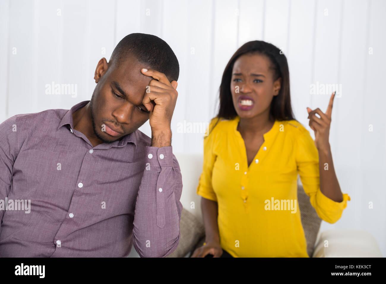 Jeune femme malheureuse having argument avec l'homme à la maison Photo Stock