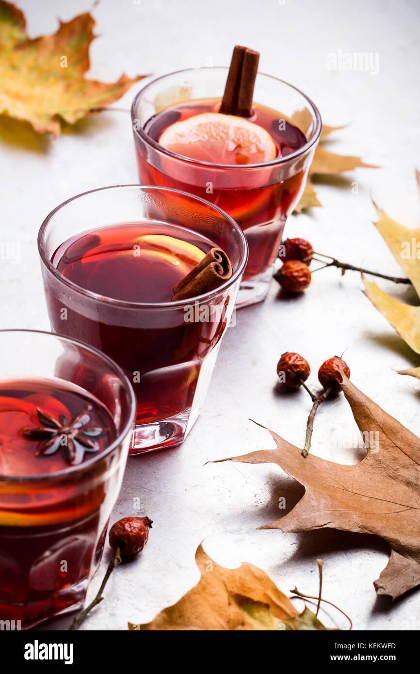 Thé rouge chaud avec du citron sur table gris clair avec copie espace, automne délicieux vin chaud verre Banque D'Images